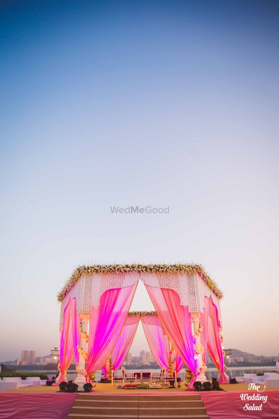 Photo of Bright Pink Outdoor Mandap with Floral Arrangement