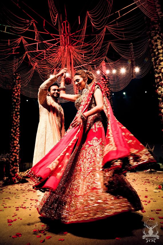Photo of bride in red bridal lehenga spinning around groom