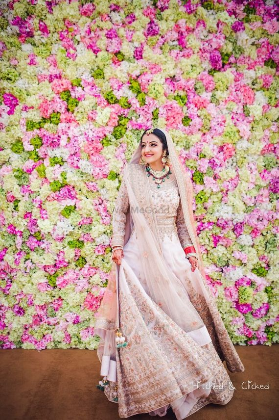 Photo of Bride wearing blush pink Anarkali against floral wall