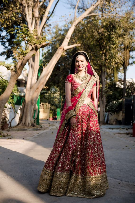 Photo of Bride Wearing Red and Gold Lehenga