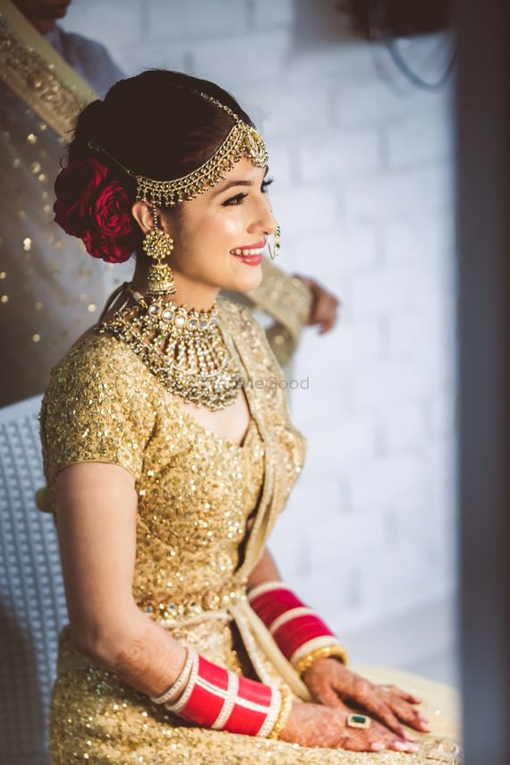 Photo of Gold bridal bun with red lips and bun