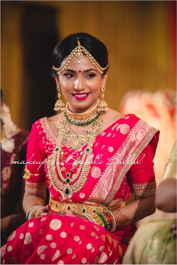 Photo of Fusion bride in red saree and layered necklaces