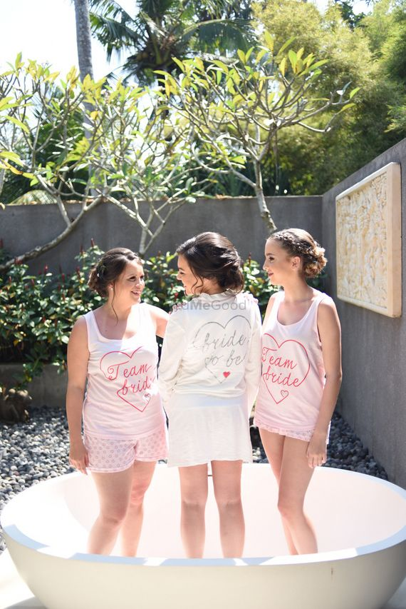 Photo of Bride in robe with bridesmaids in team bride shirts