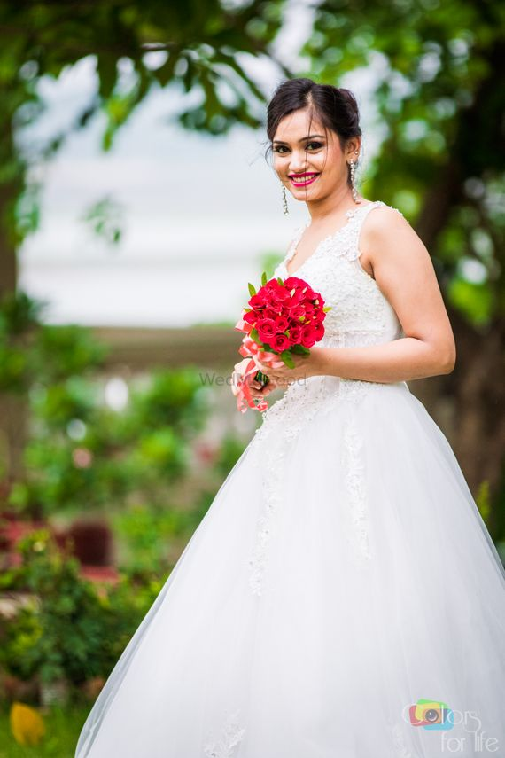 Photo of Christian Bride with White Lace Lehenga and Red Bouquet
