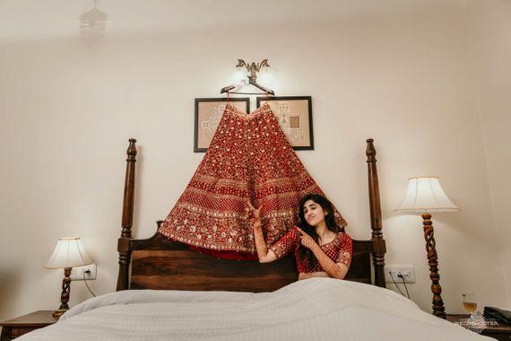 Photo of Bridal portrait idea with lehenga over bed