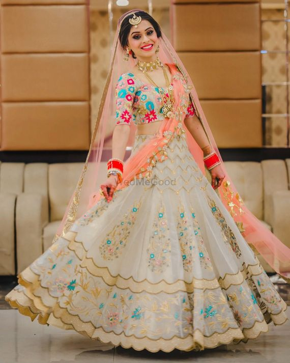 Photo of A bride in white and coral lehenga twirling