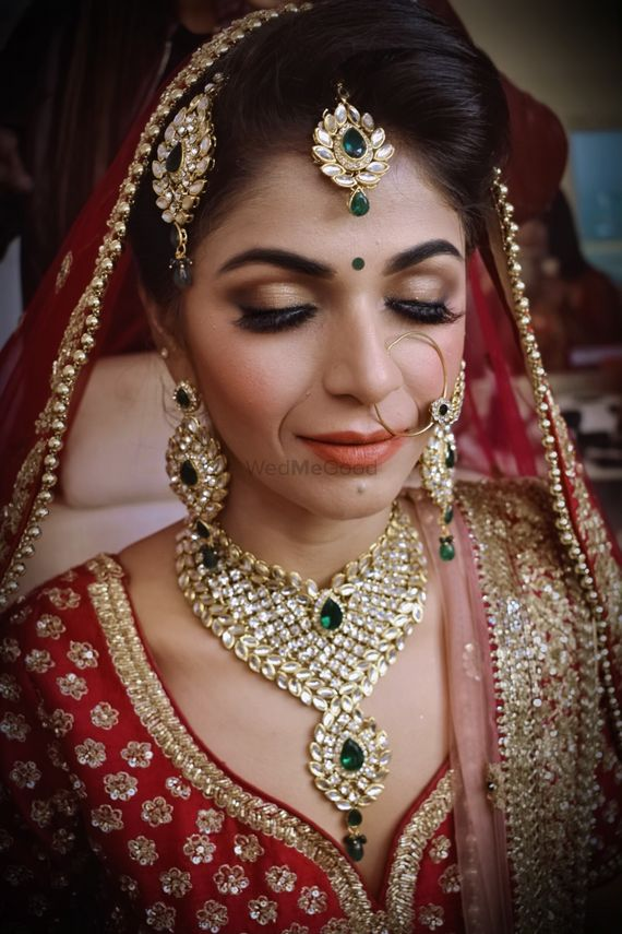 Photo of A bride in red lehenga with kundan jewelry