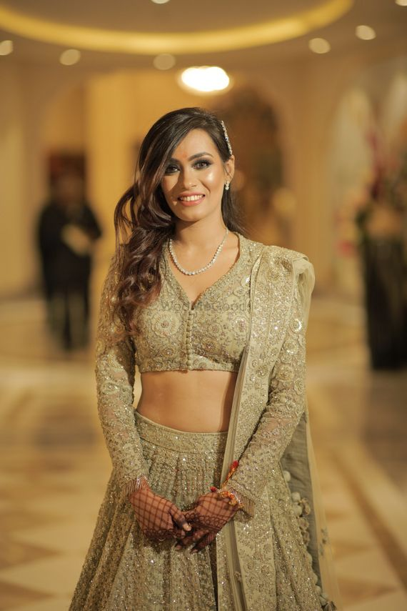 Photo of A happy bridal shot in a stunning gold lehenga and subtle makeup.