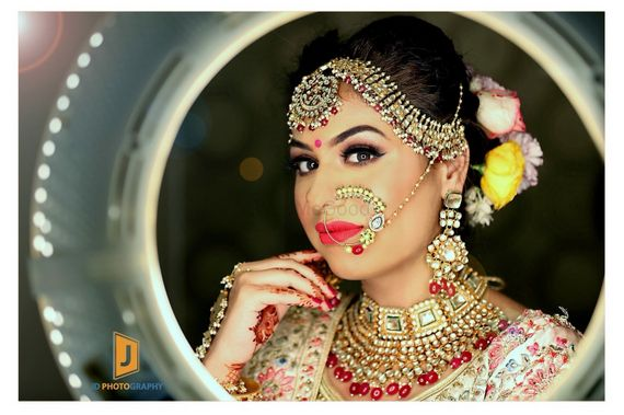 Photo of Bride with exquisite jewellery and flowers in hair
