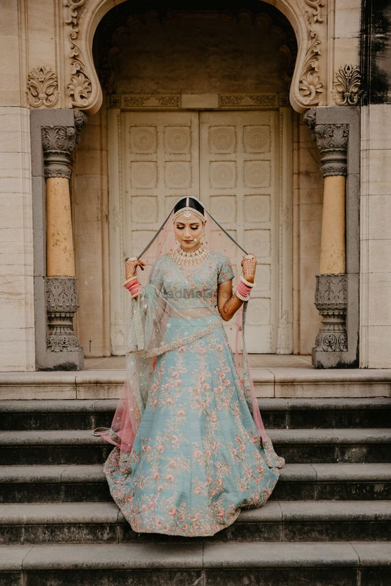 Photo of A bride in blue with a contrasting pink dupatta