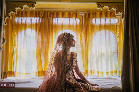 Photo of Bridal portrait with bride looking out of the window