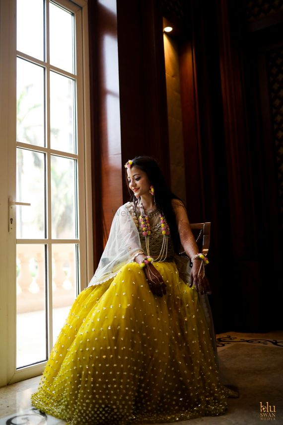 Photo of mehendi bridal look with yellow lehenga and floral jewellery