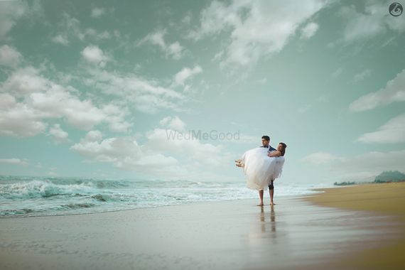 Photo of Couple Portrait on Beach with Groom Picking Bride