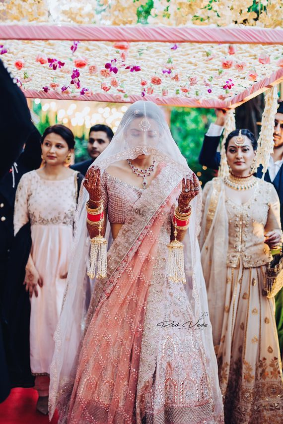Photo of A bride in a soft pink lehenga and a veil entering with her brothers and sisters