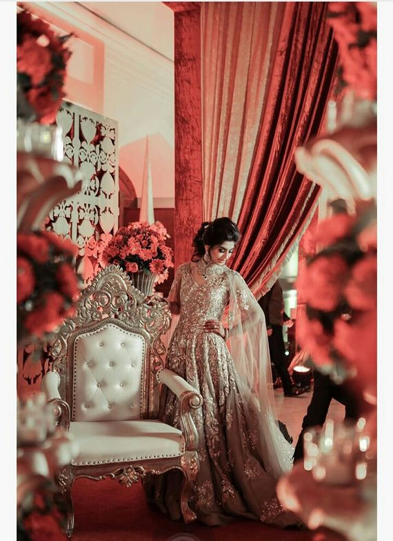 Photo of Bride posing in all gold bridal lehenga with chair