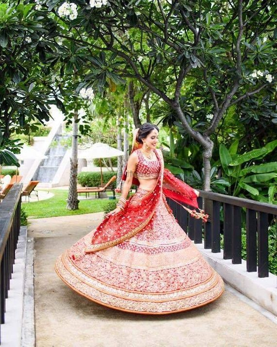 Photo of Happy bride twirling in red bridal lehenga outdoors