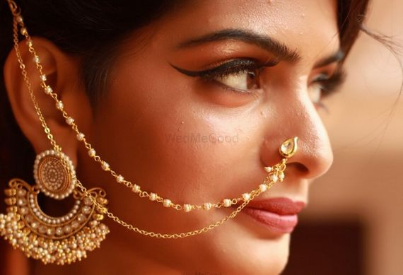 Photo of Unique gold earring attached with nath