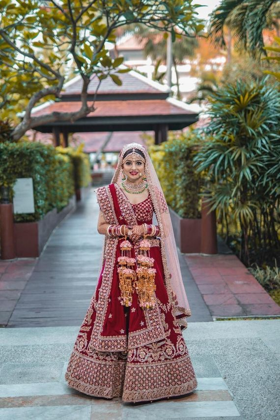 Photo of A bride in a classic maroon and gold lehenga with floral kalire