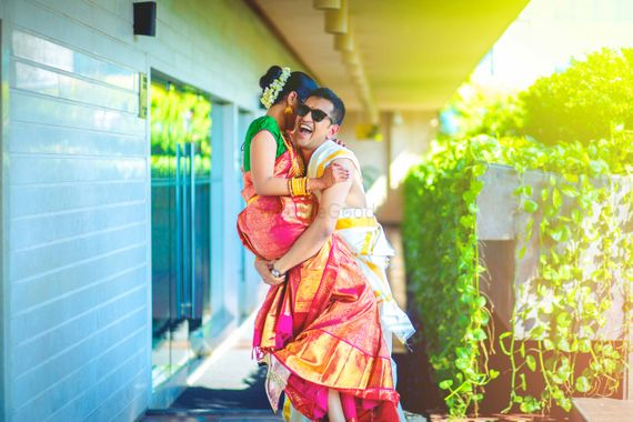 Photo of Fun south Indian couple portrait with groom picking bride