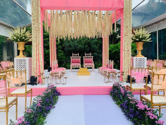 Photo of light pink mandap and aisle with floral strings