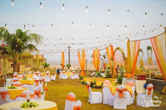 Photo of Orange and yellow theme outdoor round table setting