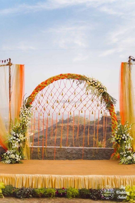 Photo of Orange and gold stage decor with jali backdrop