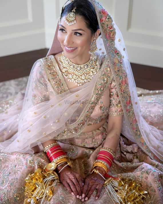 Photo of Bride in a light pink and gold lehenga with kaleere
