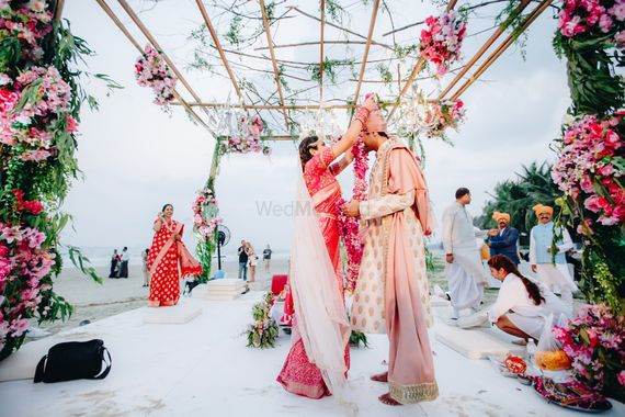Photo of A bride and groom exchange varmalas in a floral mandap