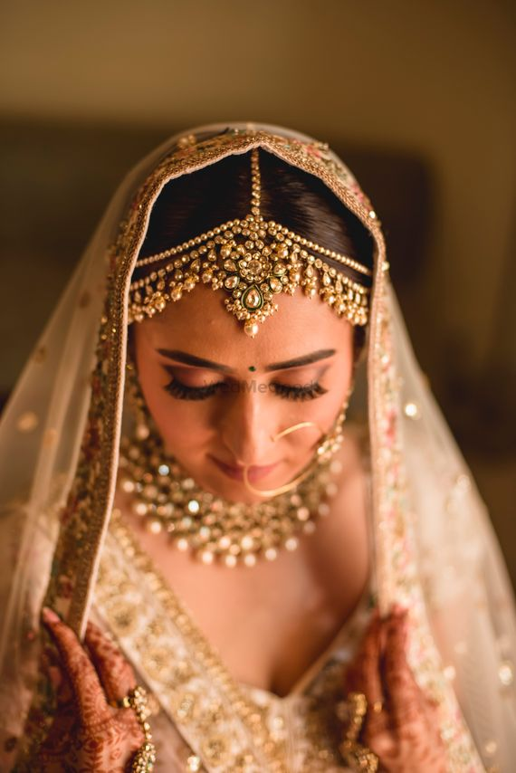 Photo of A bride in a gold lehenga with complimenting jewlery