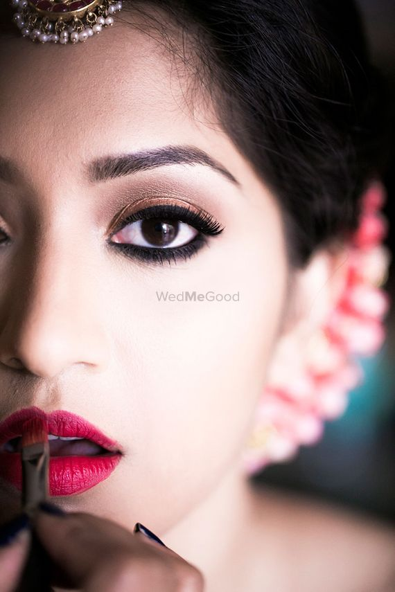 Photo of Brown eyes and matte red lips bridal makeup