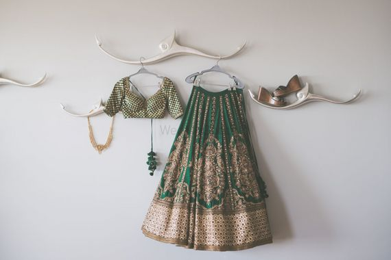 Photo of Offbeat bridal lehnega on hanger in green and gold