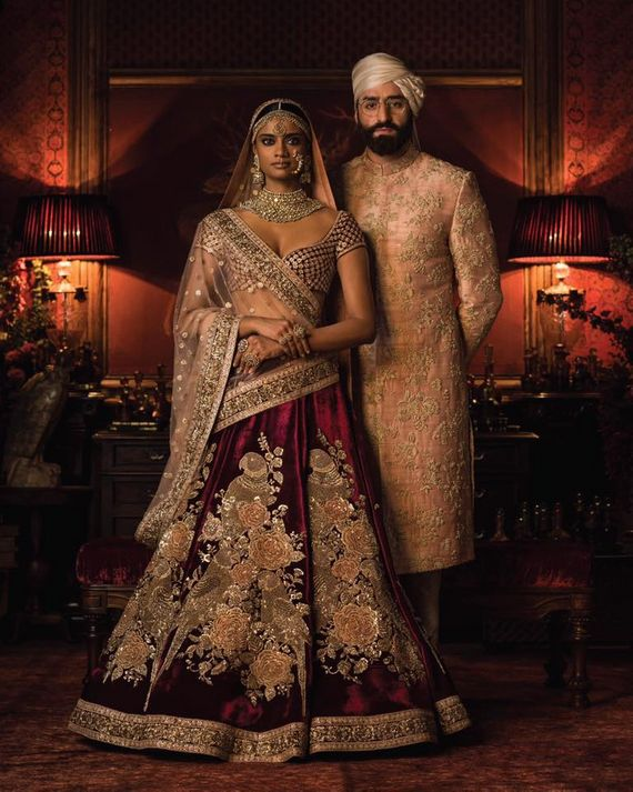 Photo of Maroon bridal lehenga and peach sherwanu sabyasachi