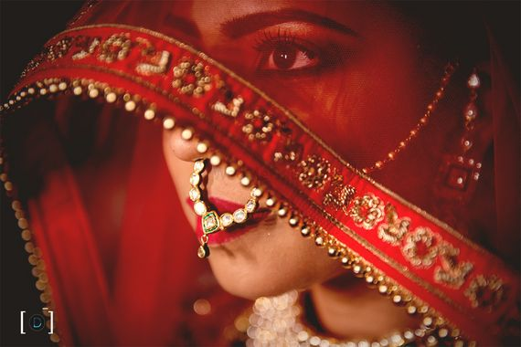 Photo of Bride in veil shot in red dupatta and nath