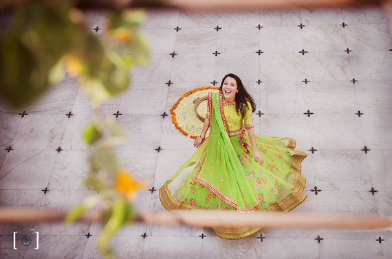 Photo of Bride twirling in green lehenga with yellow blouse