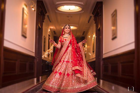 Photo of Bridal portrait twirling in red lehenga