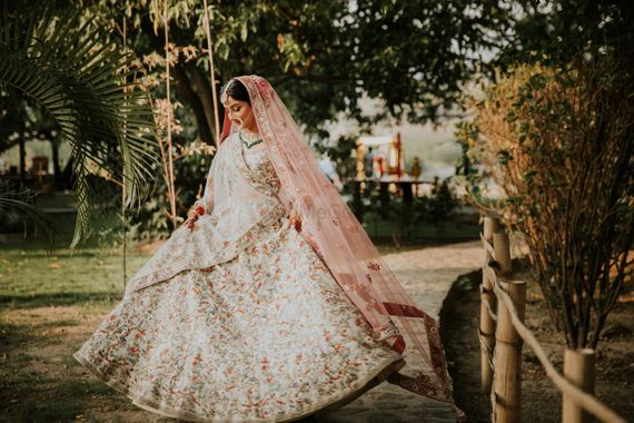 Photo of A  bride in a white lehenga with contrasting pink dupatta