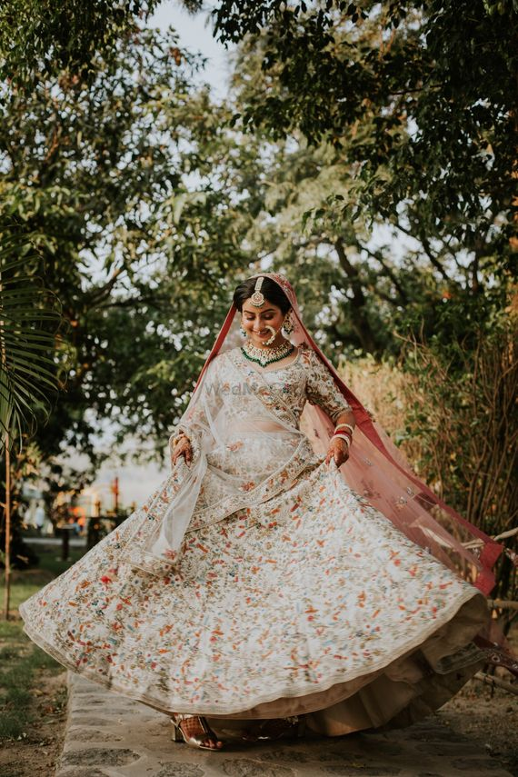 Photo of A bride in a white lehenga twirling on her wedding day