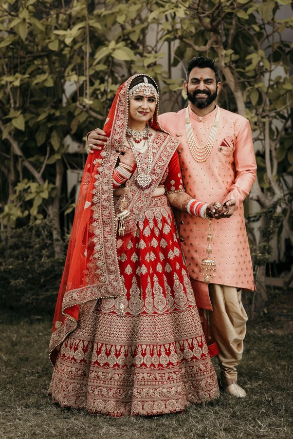 Photo of Contrasting bride and groom outfits in red and peach