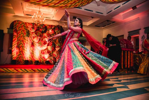 Photo of A bride in a multicolored lehenga dancing on her mehendi