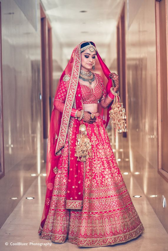 Photo of A bride in pink lehenga and golden kaleere