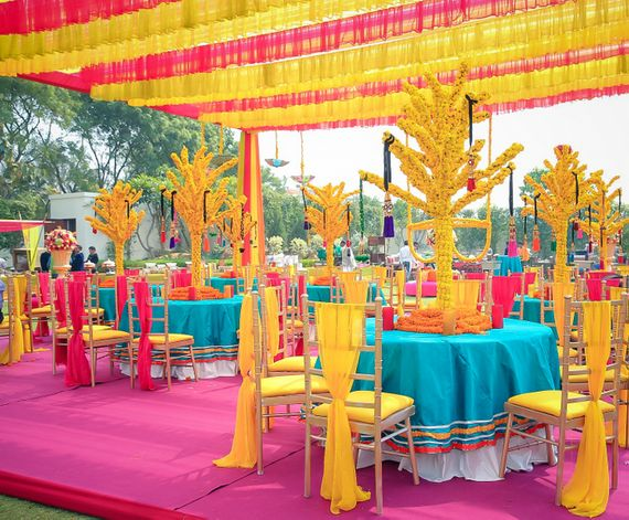 Photo of Colourful Mehendi Decor with Genda Phool Centrepiece