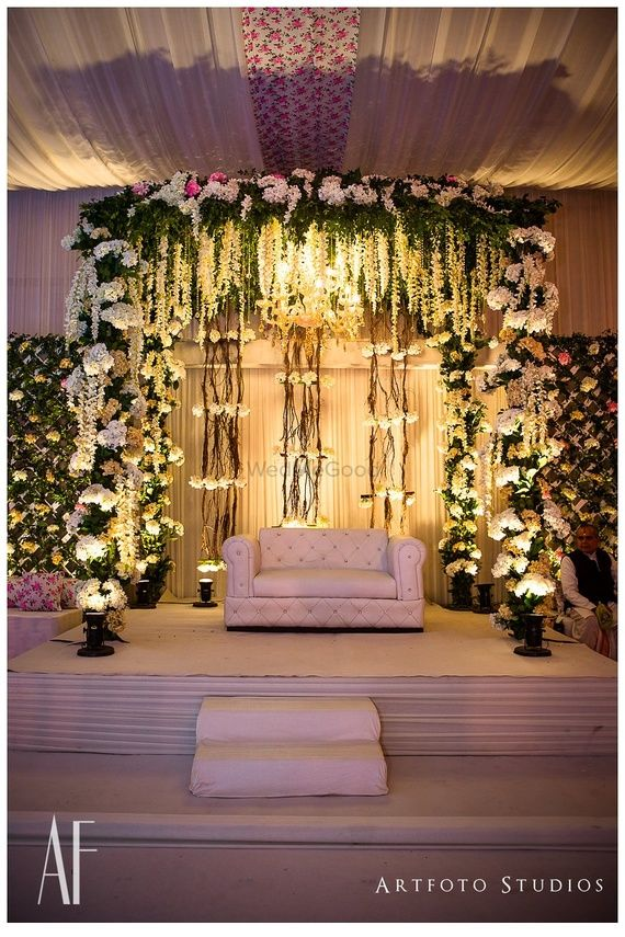 Photo of White theme floral stage decor