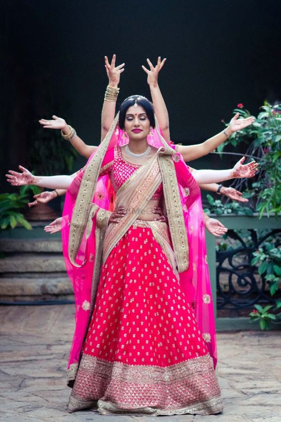 Photo of Bride in hot pink lehenga with hands sticking out
