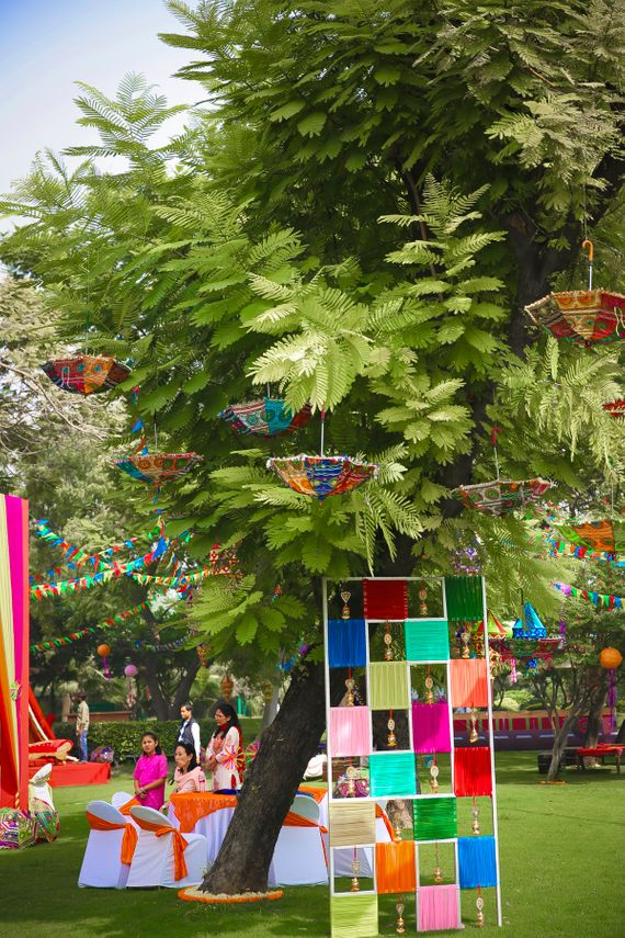 Photo of Colourful parasols and cloth decor on tree for mehendi