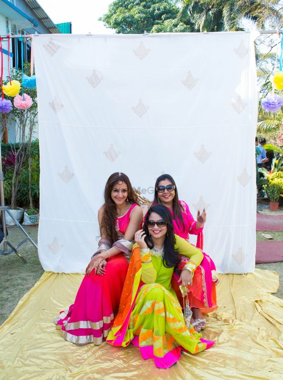 Photo of bridesmaids in bright sorbet colored outfits posing against plain white photobooth with balloons