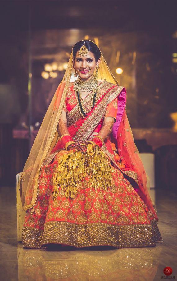 Photo of Orange and gold bridal lehenga with pink dupatta