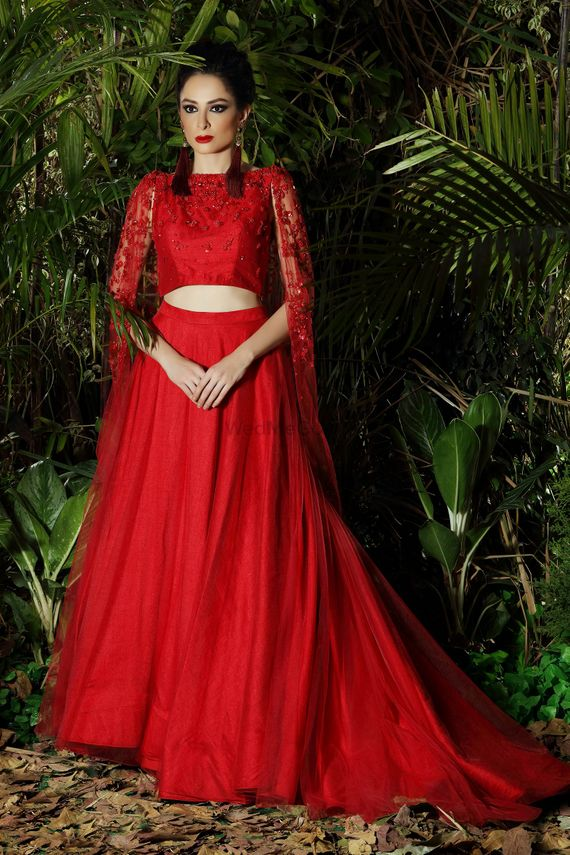 Photo of Bright red modern lehenga with lace cape and train