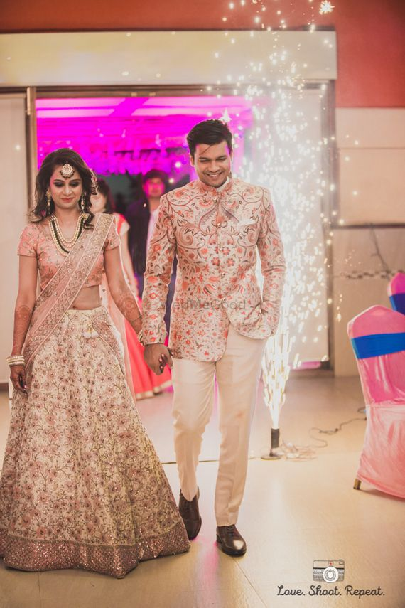Photo of Coordinated bride and groom in light peach and off white floral embroidered lehenga and jacket