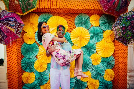 Photo of Holi party for mehendi with bride and groom against photobooth