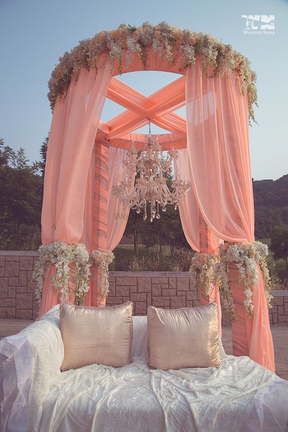 Photo of Peach mandap with curtains and chandelier